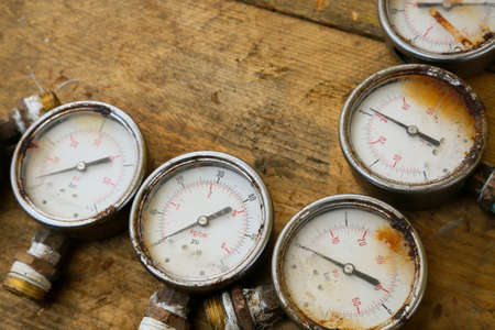 damage control: Old pressure gauge or damage pressure gauge of oil and gas industry on wooden background, Equipment of production process.