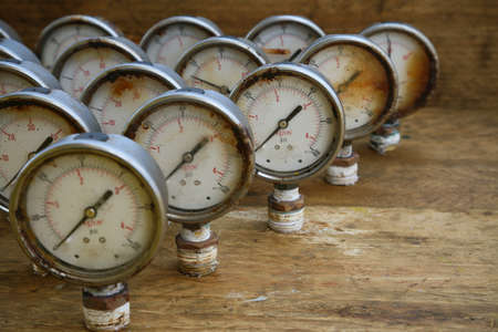 Old pressure gauge or damage pressure gauge of oil and gas industry on wooden background, Equipment of production process.