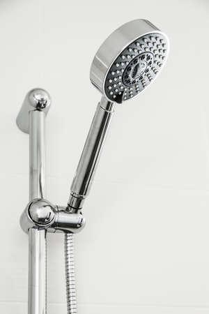 bathroom equipment: Silver shower head in bathroom with water drops flowing, Bathroom equipment. Stock Photo