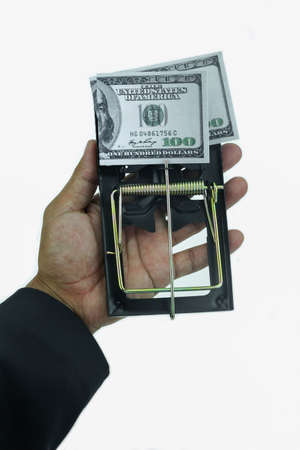 taking a risk: Trap with dollar bills isolated over white background, Risk in business, Businessman taking money from a mousetrap.