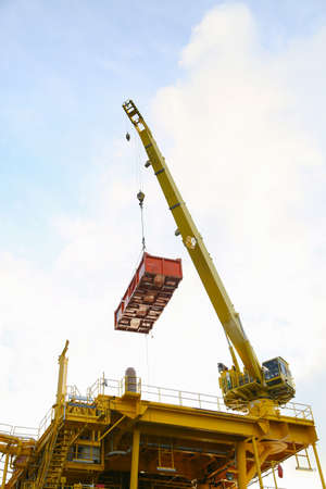 construction platform: Crane operation transfer cargo on the platform and moving cargo from supply boat, heavy lift in oil and gas construction platform. Stock Photo