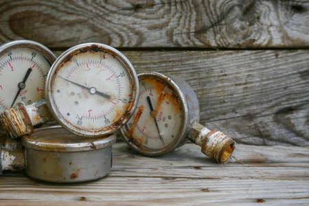 production area: Old pressure gauge on wooden background and empty area for text, damage gauge from operation oil and gas production process. Stock Photo