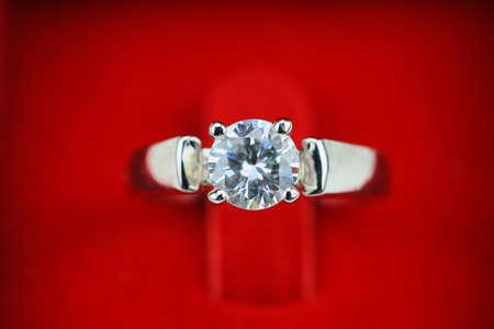simbolo: Nozze anelli di fondo, bellissimo anello d'argento nel riquadro rosso per il concetto di matrimonio.