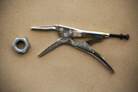 locking up: close up locking pliers on wooden background, Hand tools in work shop,