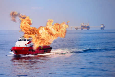 Fire burning on the boat in offshore oil and gas industry, emergency case and firefighter working for protection boat and working area.