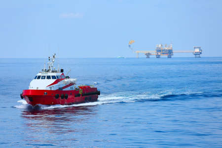 helideck: Supply boat transfer cargo to oil and gas industry and moving cargo from the boat to the platform, boat waiting transfer cargo and crews between oil and gas platform with the boat. Stock Photo