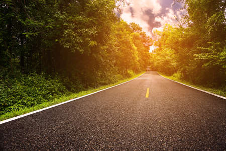 Country road between district to the city with motion blur, Journey way of traveler to the nature, Road in the mountain and the forest for travel to someplace, Asphalt road in the forest and no car. Stock Photo