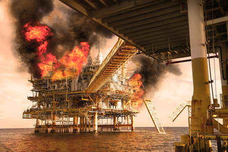 offshore oil and gas fire case or emergency case in warm picture style, firefighter operation to control fire on oil and gas production platform, offshore worst case and can't control fire 스톡 콘텐츠