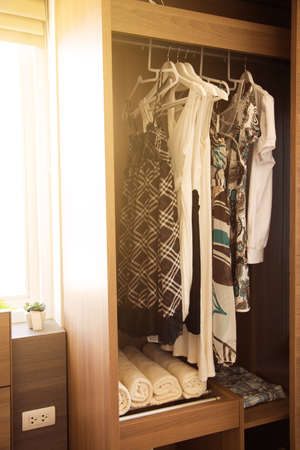 belongings: Clothes hang on a shelf in a designer clothes store, Modern closet with row of clothes hanging in wardrobe, Vintage rooms and personal belongings kept in the room which feeling luxury and relax.