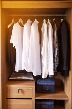 hook like: Clothes hang on a shelf in a designer clothes store, Modern closet with row of clothes hanging in wardrobe, Vintage rooms and personal belongings kept in the room which feeling luxury and relax.