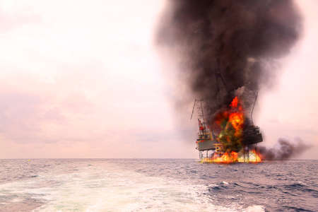 Offshore oil and rig construction damaged because worst case or fire case which cant control situation. Oil spill into the sea because incorrect of operation and accident in job out of safety rule. Stock Photo