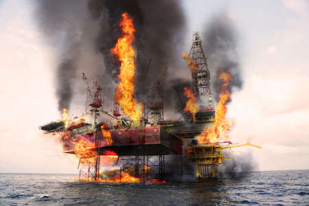Offshore oil and rig construction damaged because worst case or fire case which cant control situation. Oil spill into the sea because incorrect of operation and accident in job out of safety rule. Zdjęcie Seryjne