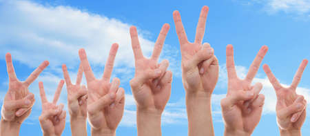 Teenagers raising their hands with two finger symbolizing peace photo