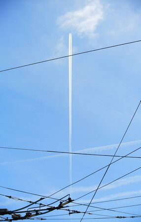 contrail: Center flying plane contrail aligning with cables over sky Stock Photo
