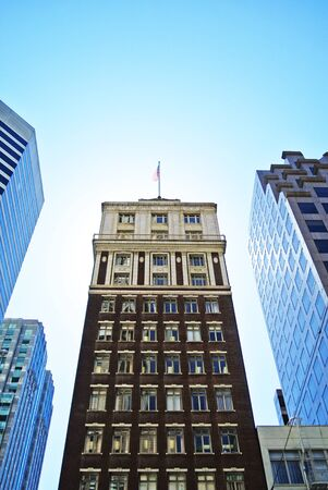 standing out: Classic powerful building with american flag standing out among different architecture Stock Photo