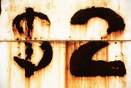 money to burn: Photo of burned two dollar sign over rusty eroded wall Stock Photo