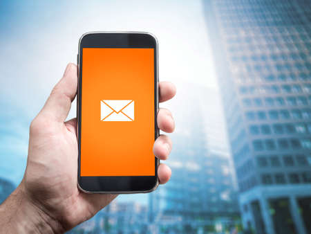 message box: Hand holding mobile smart phone with message on a screen. E mail icon, Office buildings background Stock Photo