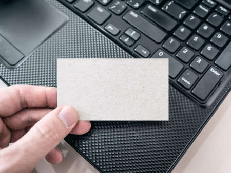Man Holding a Blank Cardboard Business Card and Using Modern Laptop