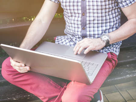 watch city: Young Man wearing in shirt sitting in city park and writing on his laptop, watch on wrist Stock Photo