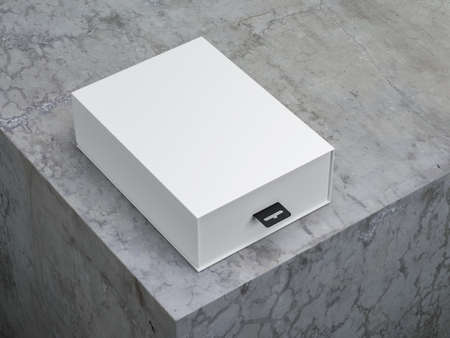 Close up of White box packaging with black hang tab on concrete table