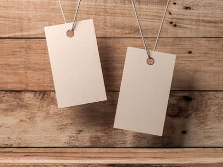 Two Empty kraft paper tags label Mockup tied by rope on wooden box