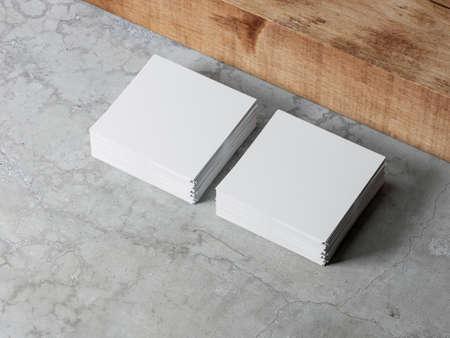 Des piles de maquettes de feuilles de papier carrées blanches sur un sol en béton