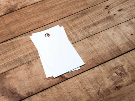 Two White textured tags or labels Mockup on wooden table