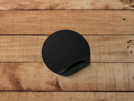 Black round adhesive sticker mockup on wooden table