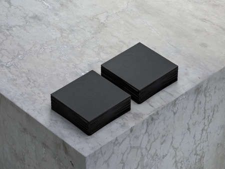 Two stacks of black textured square paper sheets mockup on concrete cube