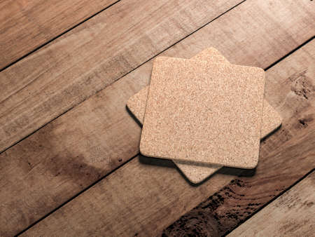 Two square Cork beer coasters Mockup lies on the wooden table