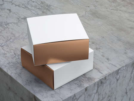 Two square golden boxes with white covers on concrete table