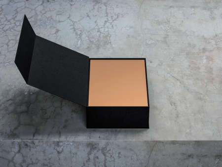 Open black cardboard box on concrete table with golden paper inside