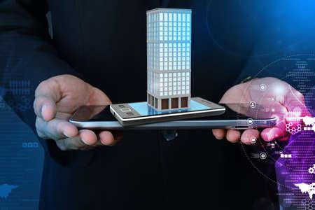 fiestas electronicas: La mano inteligente que muestra el tel�fono inteligente con el concepto de las propiedades inmobiliarias