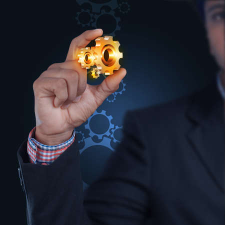 gears and cogs: businessman showing gears cogs to success concept