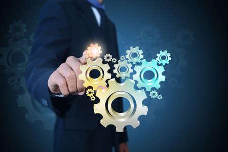 herramientas de mecánica: hombre de negocios que muestra los engranajes engranajes al concepto de éxito