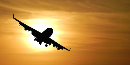 flights: The silhouette of the plane against the sun. Stock Photo