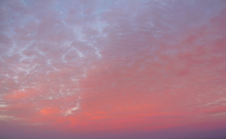 Pink, cirrus clouds against the evening sunset.