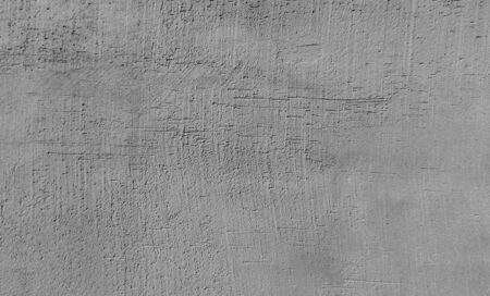 Texture of gray, unpainted plaster on the wall.