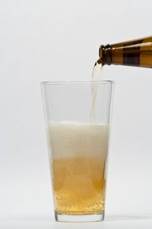 Pouring beer into a glass Imagens