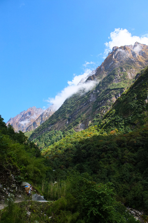 A porter carrying trekkers belongings and walking into a very beautiful valley in Nepal