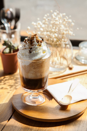 Capuchino coffee shop dessert recipe, whipping cream topping; lay on wooden plate and spoon. chilling on sunny day.