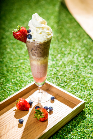 Mix berry shake smoothie tower recipe; therere strawberry, blueberry, banana, chocolate. Wooden tray on grass display.