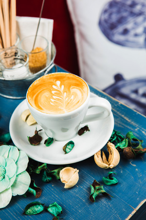 Coffee cup latte foam arts in heart shape with porps by stylist, lay on blue wood table. Stock Photo