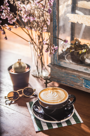 Coffee cup latte arts vintage mood, sweet sepia retro light with old glass lamp, cactus; dried flowers on wood table.