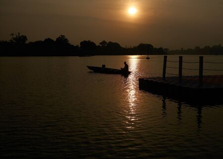 Silhouette of indonesian fisherman on wooden boat. fisherman go away from dock in the beautiful sunset 免版税图像