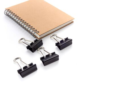 Office desktop with group of Black metal binder paper clip clamps and note book isolated on white - image