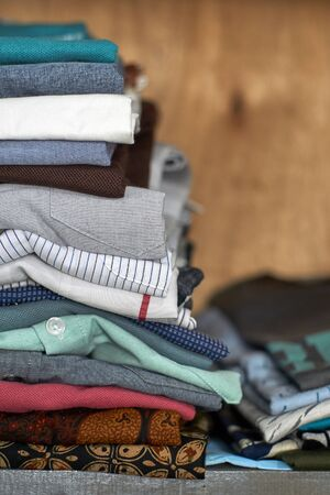 Choice of clothes in different style piled up in wooden cabinets 스톡 콘텐츠