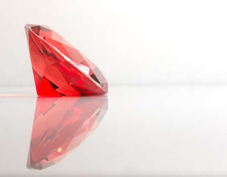 Faceted Red Round Gemstone with Reflection on White Background