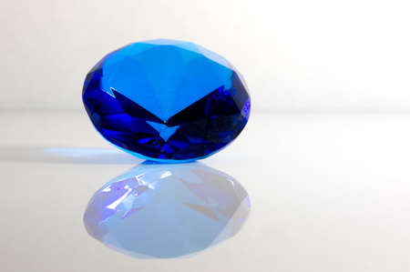 Faceted Round Blue Sapphire Gemstone on White Background photo