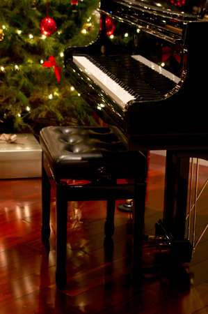 Baby grand piano with Christmas tree & presents in background